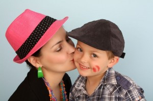 Woman in hat kissing a child on the cheek
