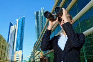 Man in City Looking Through Binoculars